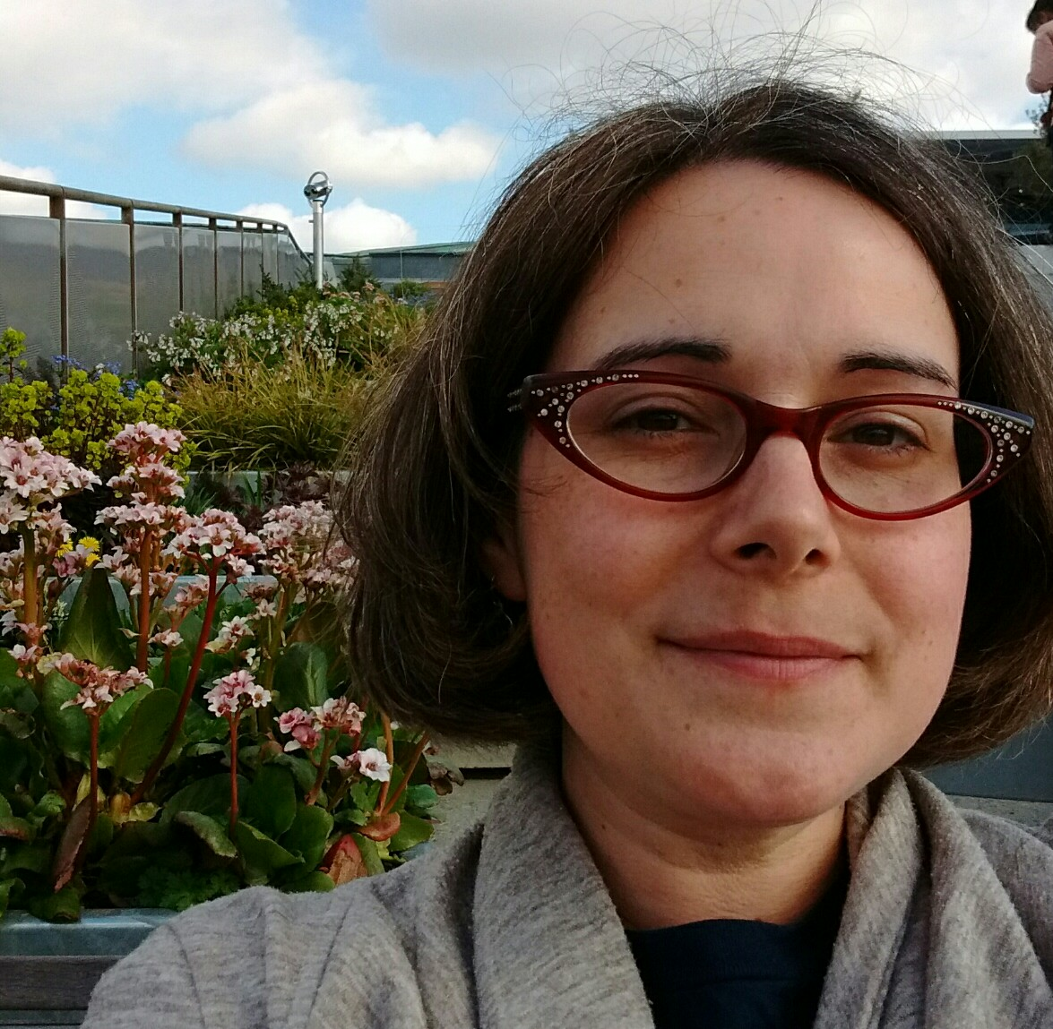 A Woman with glasses and brown hair with flowers and clouds in the background