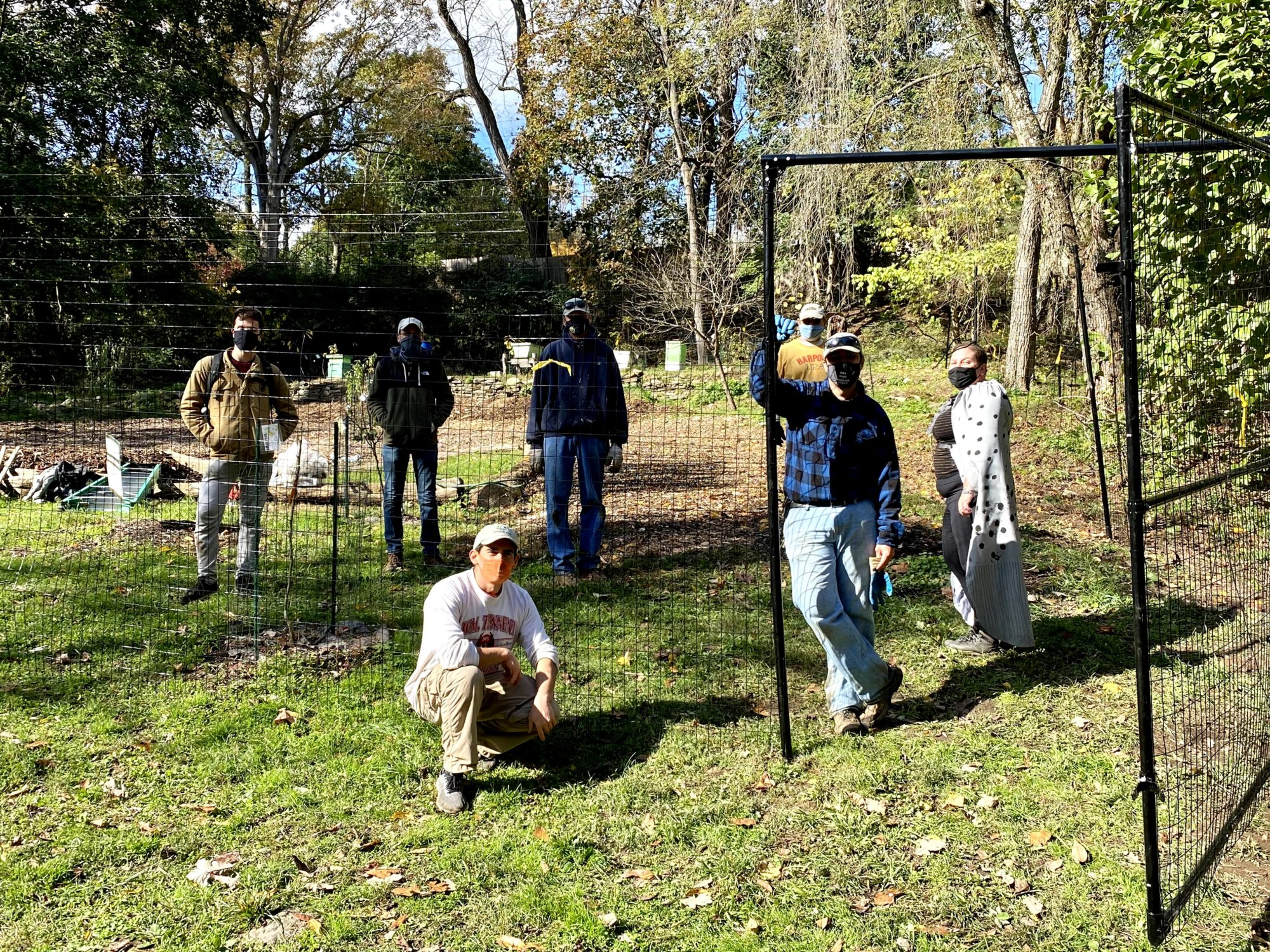 WEC's team posing behind the newly-constructed fencing which will protect the growing Food Forest from hungry deer