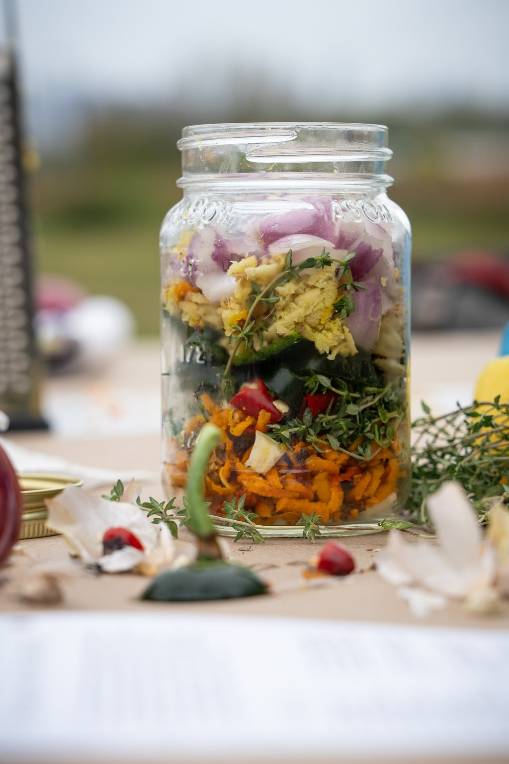Layers upon layers of fresh colorful medicinal herbs and spices fill a glass jar from this Fire Cider workshop at Bartram's Garden in November 2020. Photo by Marc Steiner.