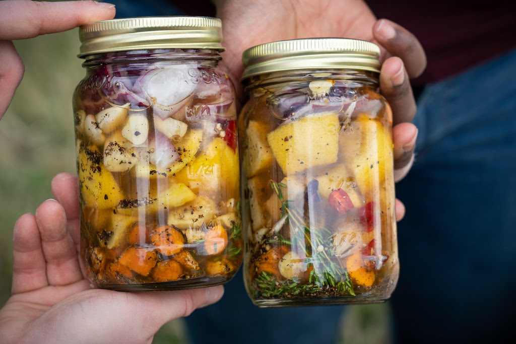 Two colorful jars of freshly prepared fire cider.