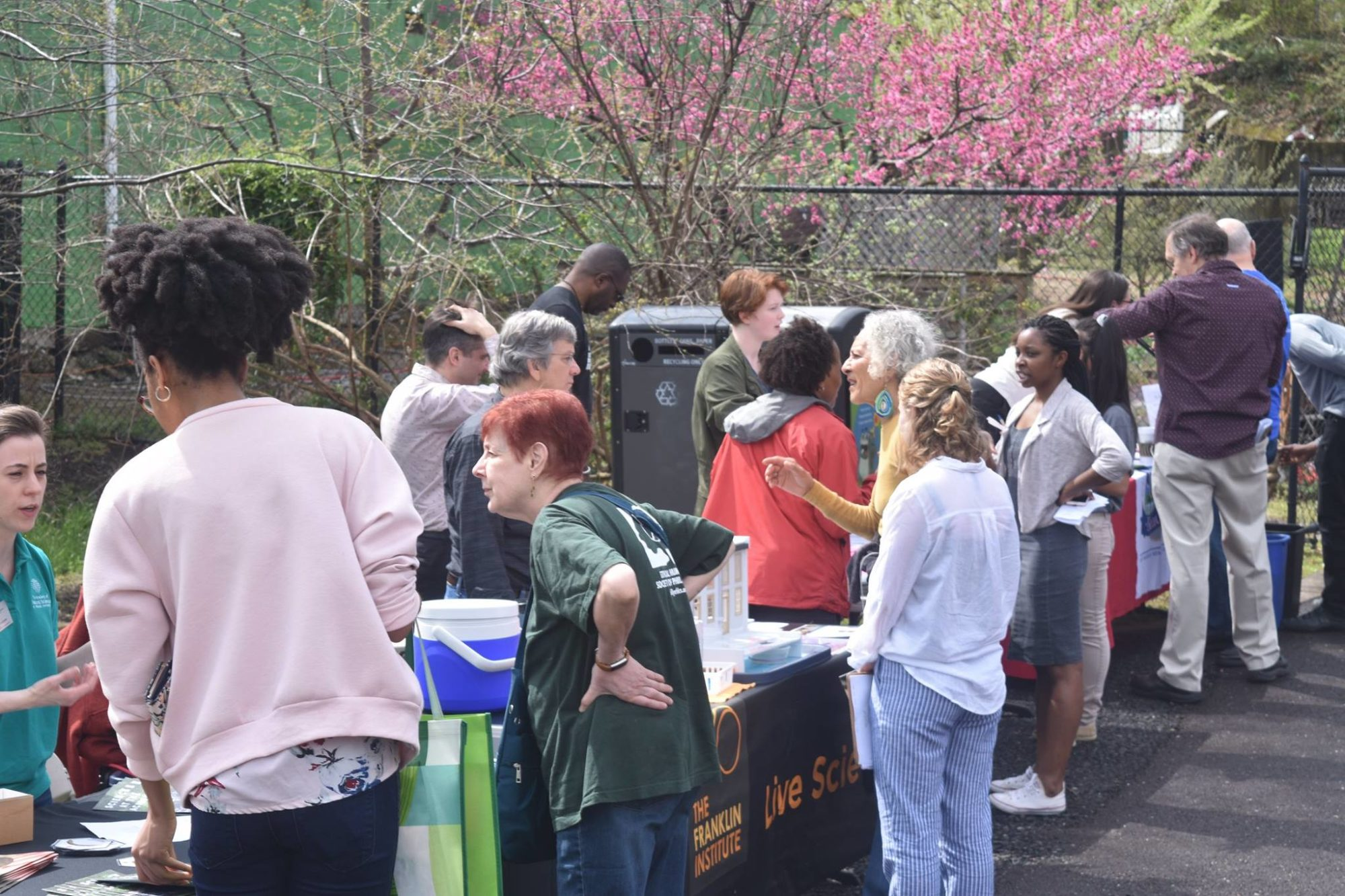 A community event outside OEEC in April 2019, where partners and collaborators came to engage with community members about environmental issues in celebration of Earth Day (photo courtesy OEEC). Visitors surround a row of tables with information and demonstration items on them, and there is a tree in bloom in the background.