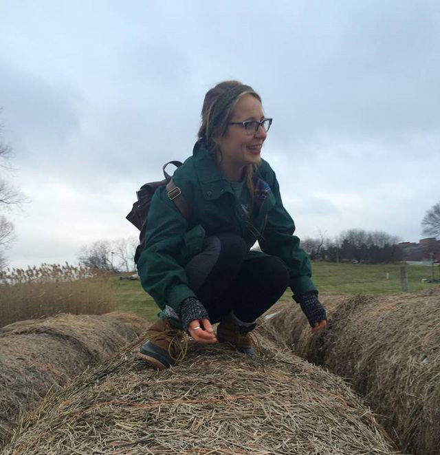 A woman wearing a green coat, boots and glasses, smiles while crouching down on a bale of hay
