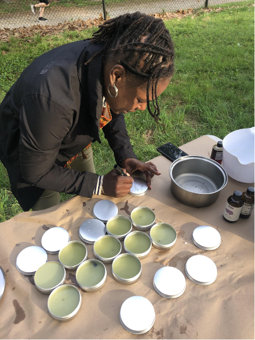 Nyambi labels metal tins filled with herbal salve at a May 2021 workshop. Photo credit:POP.